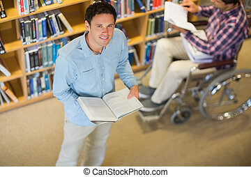 Man by disabled student in wheelchair in the library