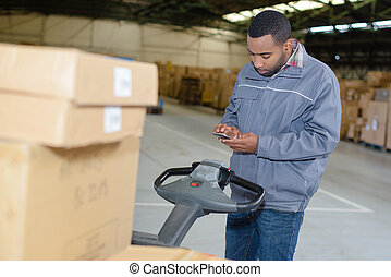Man by pallet truck, using mobile phone