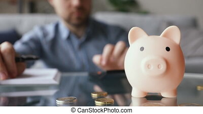 On background man calculates writing in daily planner personal expenses and incomes, close up focus on piggy bank euro coins on table, symbol of budget managing, make savings and take care of tomorrow