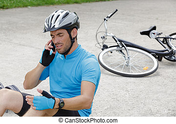 man calling emergency after fall from bicycle