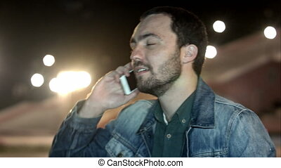 Man calling on mobile phone at night city