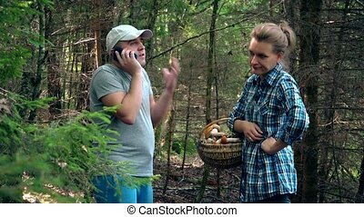Man calling phone. Upset woman standing with basket full of mushrooms