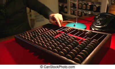 Man calling the old phone, wooden abacus in the office