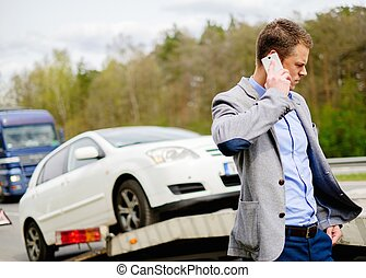 Man calling while tow truck picking up his broken car