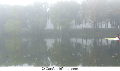 Man canoe waters fog - Man paddles a red canoe across the...