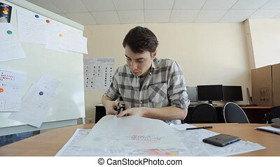 Man carefully cuts carbon paper with black layout of...