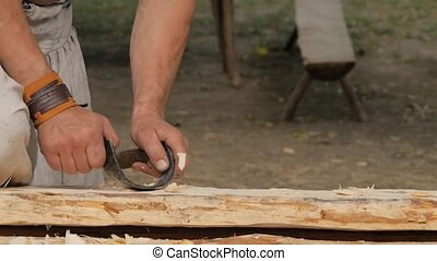 Man carpenter using drawknife - vintage analogue of spokeshave and plane to shape and smooth wood board at summer historical medival festival - close up, slow motion. Craftsmanship, handwork concept