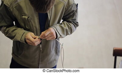 Man carries out the designation of phasing on a white wire.