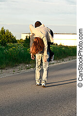 Man carring a young woman on his shoulder.