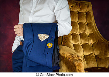 man carris jacket suit standing beside sofa
