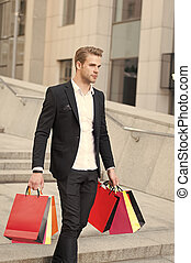 Man carry shopping bags on urban backdrop. Businessman with package walk in street. Fashion shopper with paperbags. Great day for shopping. Big sale on black friday. Man bought many birthday presents.