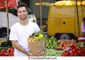 Man carrying a shopping paper bag full of fruits and vegetables at an open street market.
