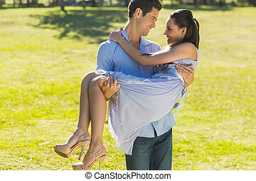 Man carrying a woman in park