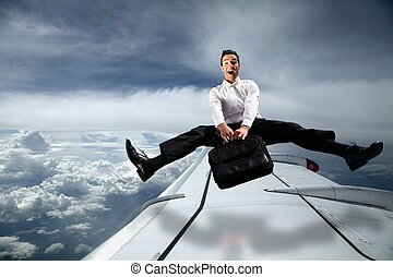 man carrying bag in sky above plane with legs wide apart