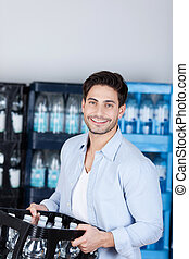 Man Carrying Crate Of Water Bottles In Store