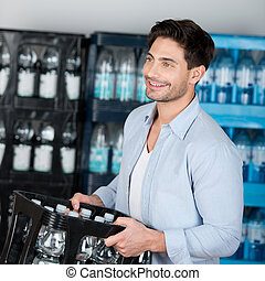 Man Carrying Crate Of Water Bottles While Looking Away In Store