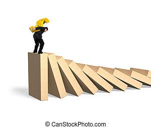 Man carrying dollar symbol standing on falling dominoes