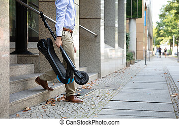 Man Carrying E-Scooter From Work
