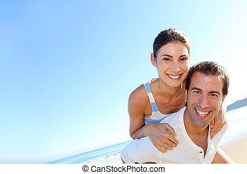 Man carrying girlfriend on his back at the beach