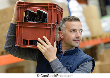 man carrying glass bottles of craft lager beer