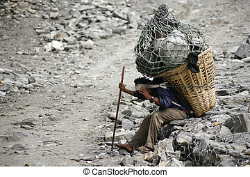 man carrying heavy load, annapurna, nepal
