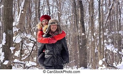 Man carrying his woman piggyback on a winter day in a joyful...