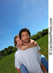 Man carrying little girl on his back in a meadow