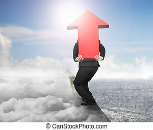 Man carrying red arrow sign on ridge with cloudscape cityscape
