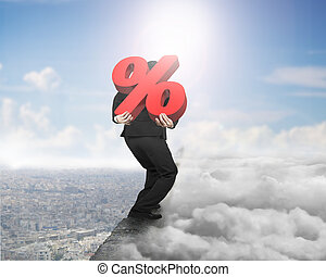 Man carrying red percentage sign on ridge with cloudscape...