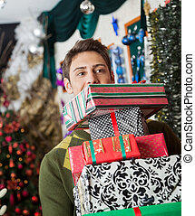 Man Carrying Stacked Christmas Gifts In Store