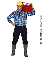 Man carrying tool box on shoulders