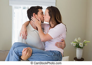 Man carrying woman as he kisses her