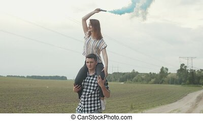 Man carrying woman with smoke bomb on shoulders - Handsome...