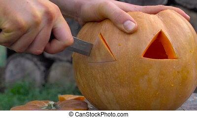 Man carves from a pumpkin Jack-o'-lantern in the backyard on a tree stump