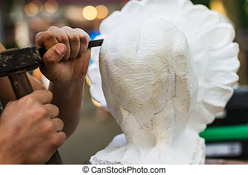 Man carving stone statue - Young student at work learning...