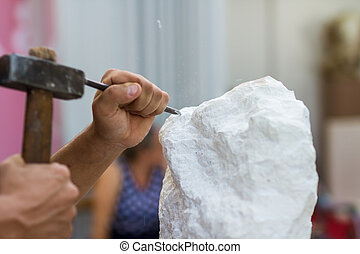 Man carving stone statue - Young student at work learning ...