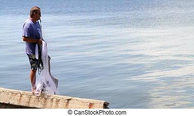 Man Casting Seine Net - Barefoot fisherman stands on seawall...