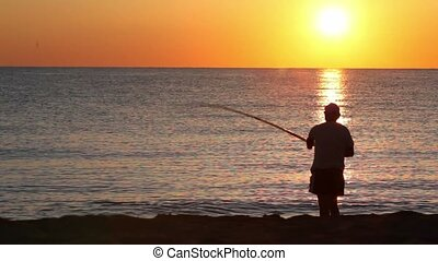 Man casts a fishing rod, and then beckoning fish, on sea at...