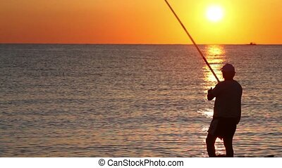 Man casts a fishing rod, and then beckoning fish, fishing...