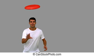 Man catching a frisbee on grey screen