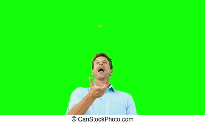 Man catching an orange segment in mouth - Man catching an...