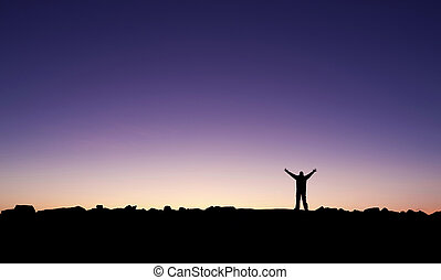 Silhouette of a man raising his hands into the sunrise after conquering a summit