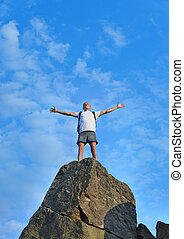Man celebrating reaching the top of a mountain standing on...