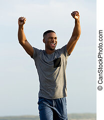 Man celebrating success with arms raised