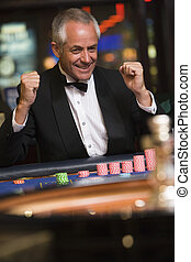 Man celebrating win at roulette table in casino