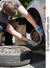 Man changing a car brakes