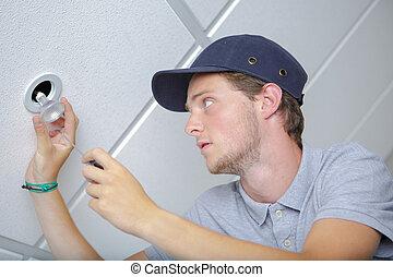 man changing a lightbulb