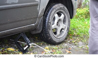 Man changing a rear wheel of car - Changing a car wheel:...