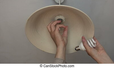 Man changing light bulbs in a lamp - Man changing an...