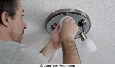 Man Changing Lightbulb on Ceiling Fixture Closeup - Close up...
